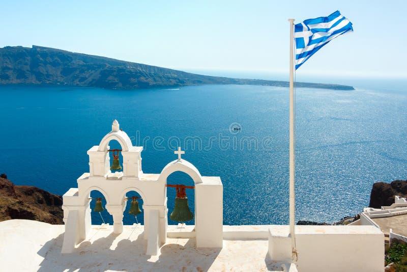 钟楼和希腊旗子在圣托里尼 库存照片