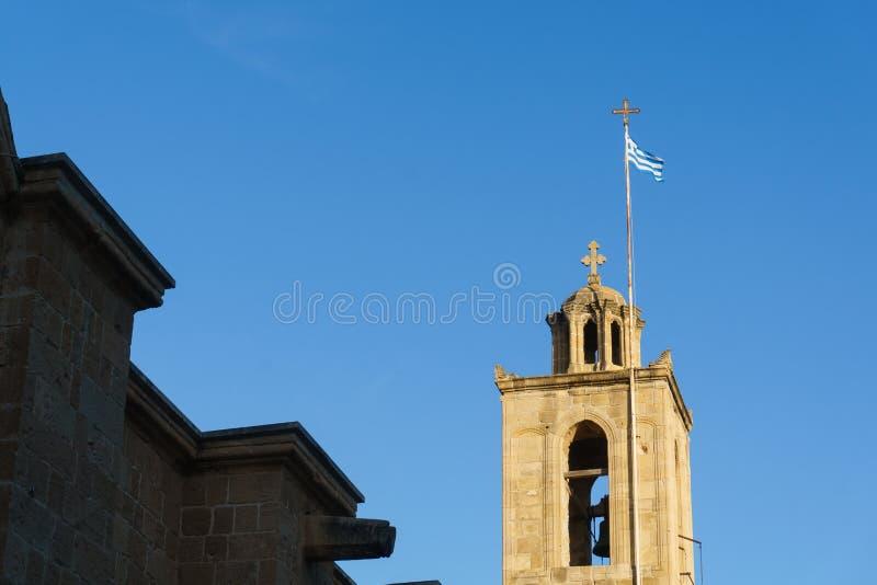 钟楼照片与希腊旗子的反对蓝天 库存照片
