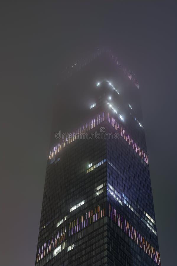 钢和玻璃片段现代海拔办公楼抽象高科技背景与在晚上被交换的光在 免版税库存照片