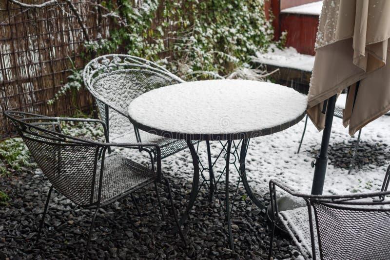 钢庭院桌和椅子在雪下 库存照片