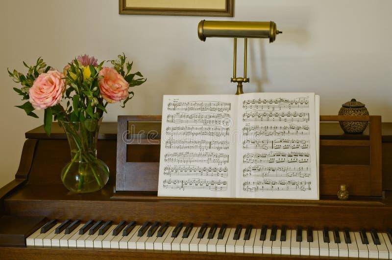 钢琴依然生活着鲜花、灯和音乐 免版税库存图片
