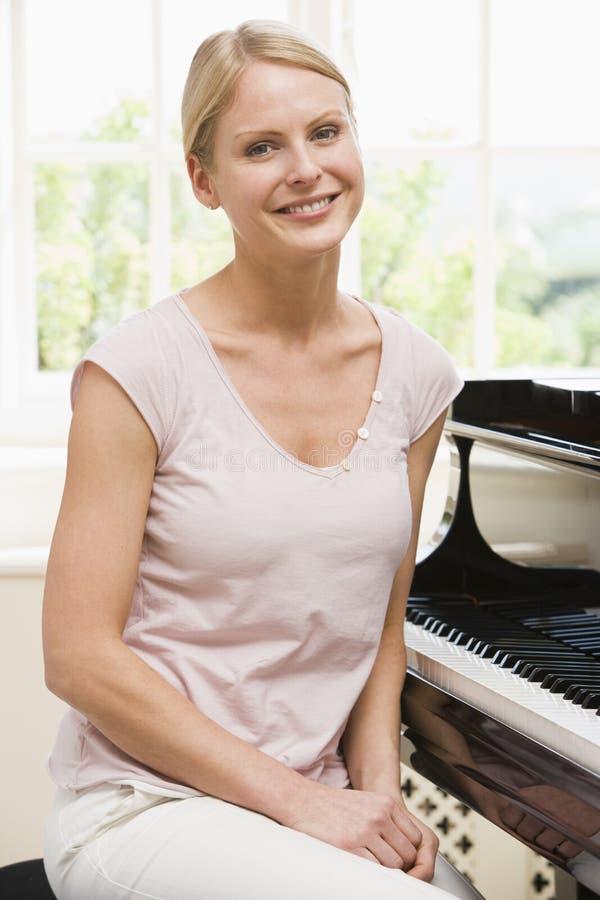 钢琴坐的妇女 免版税图库摄影