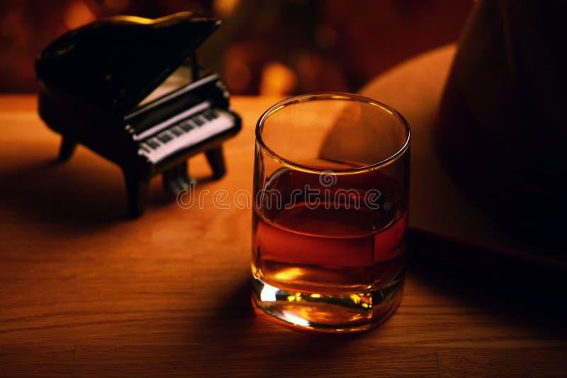钢琴威士忌酒玻璃葡萄酒帽子木桌金bokeh 免版税库存照片