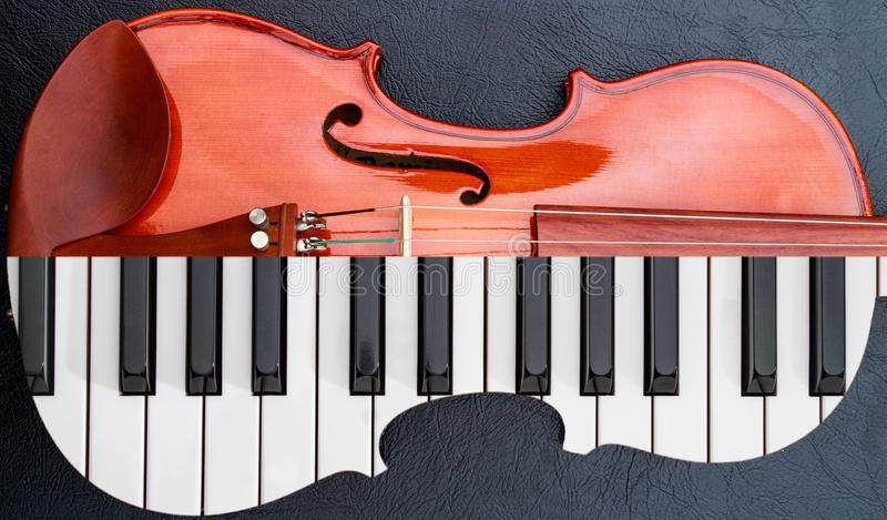 钢琴钥匙到在黑皮革桌上的小提琴,半键盘喜欢小提琴形状 库存照片