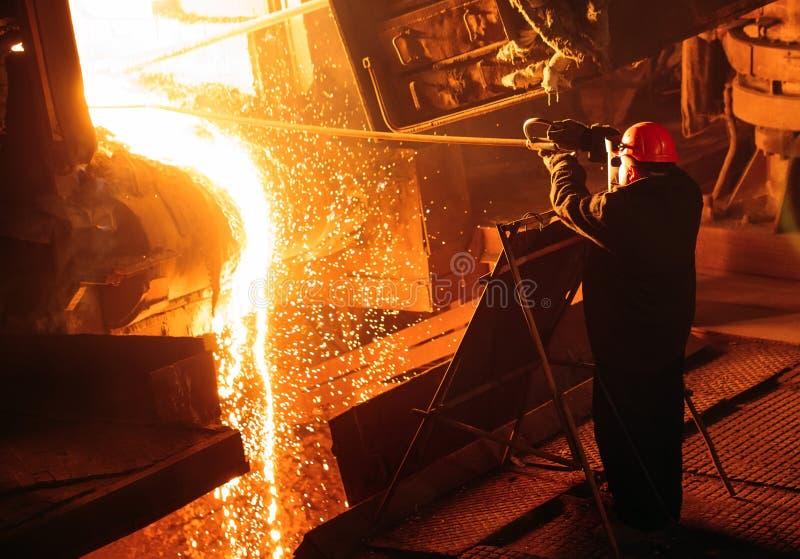 钢的生产的植物 电熔化炉 工厂劳工采取金属的一个样品 免版税库存照片