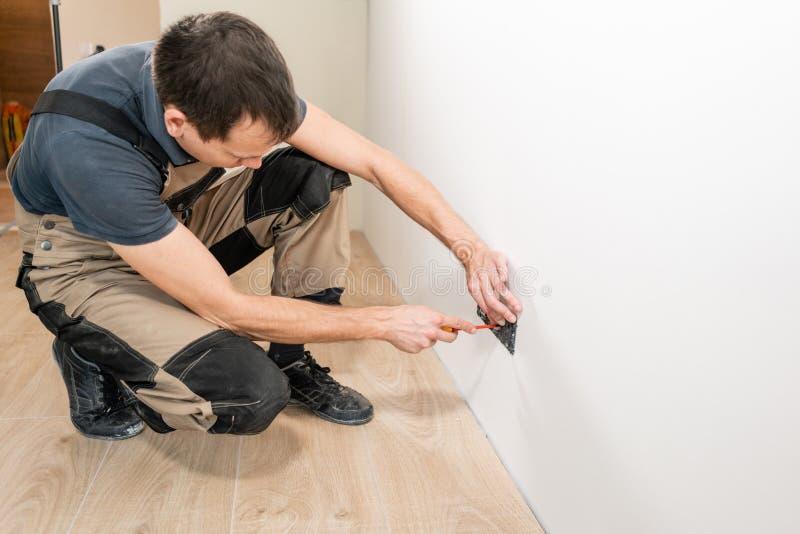 钢缆和灯开关或力量的一名电工工作者壁装电源插座插口设施工作 图库摄影