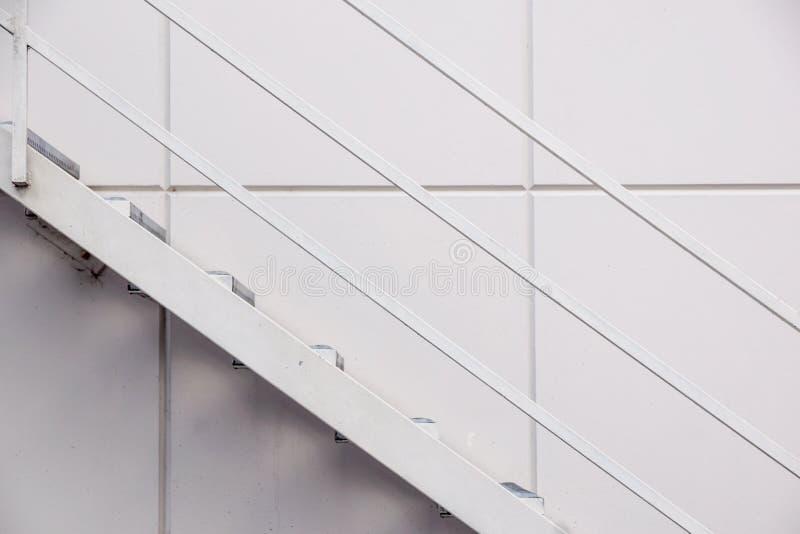 钢铁生产厂梯子,在银色金属板墙壁前面的太平门梯子 库存图片