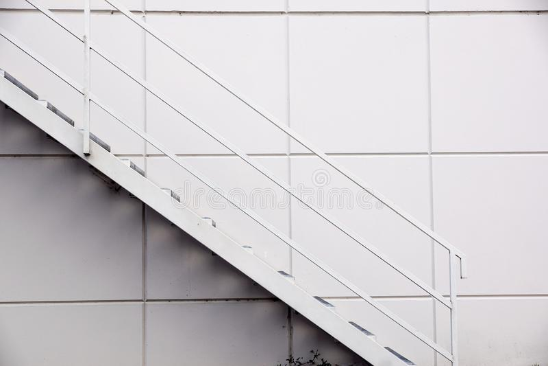 钢铁生产厂梯子,在银色金属板墙壁前面的太平门梯子 库存照片