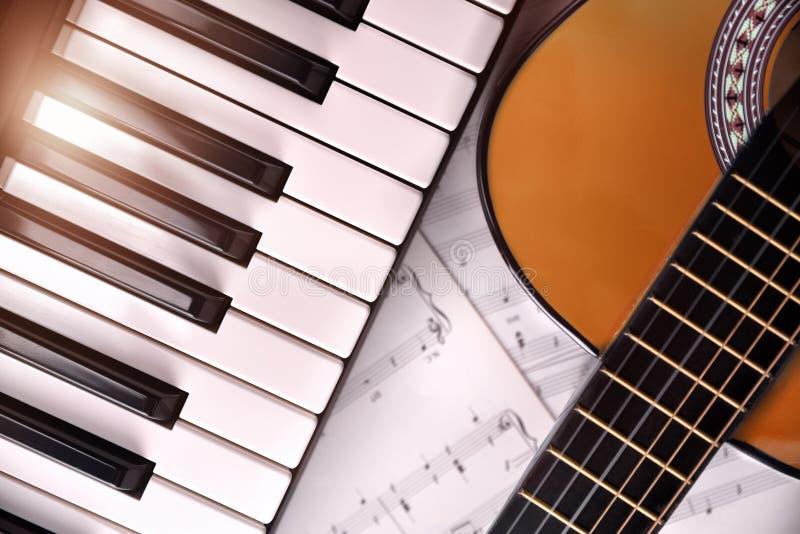 钢琴和吉他有亮光和活页乐谱背景冠上 库存图片