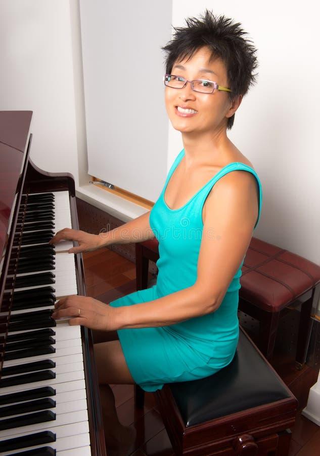 钢琴的亚裔妇女 库存照片