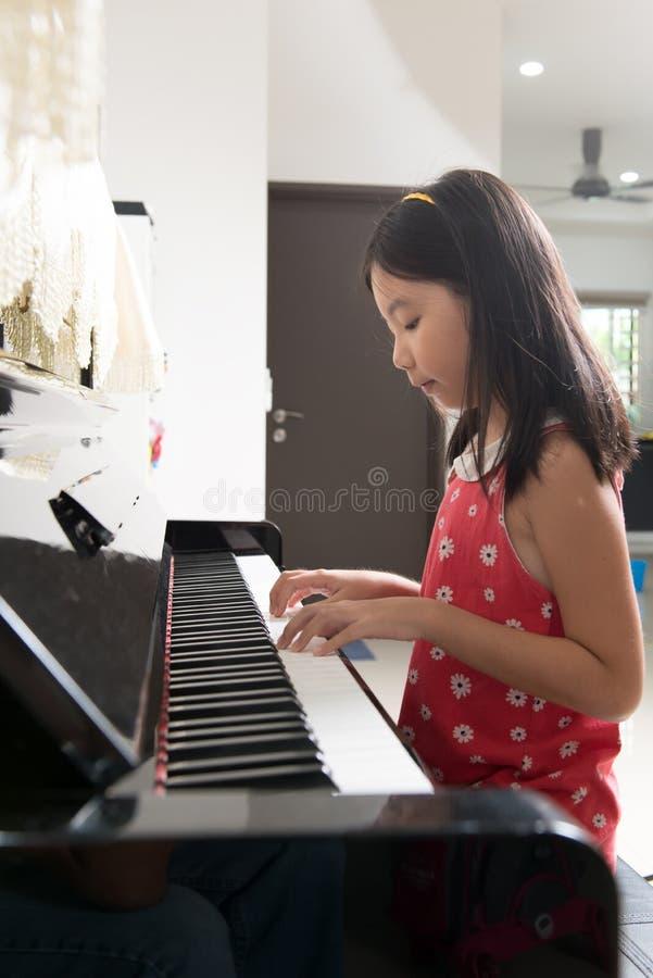 钢琴的小亚裔女孩 免版税库存图片