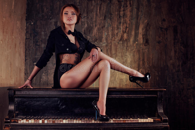 钢琴的性感的妇女 免版税库存照片