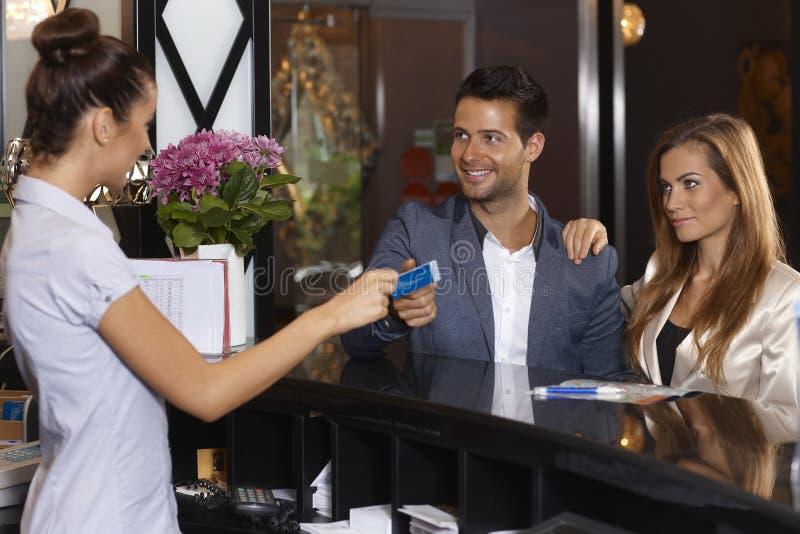 给钥匙卡片的接待员客人在旅馆 免版税库存照片