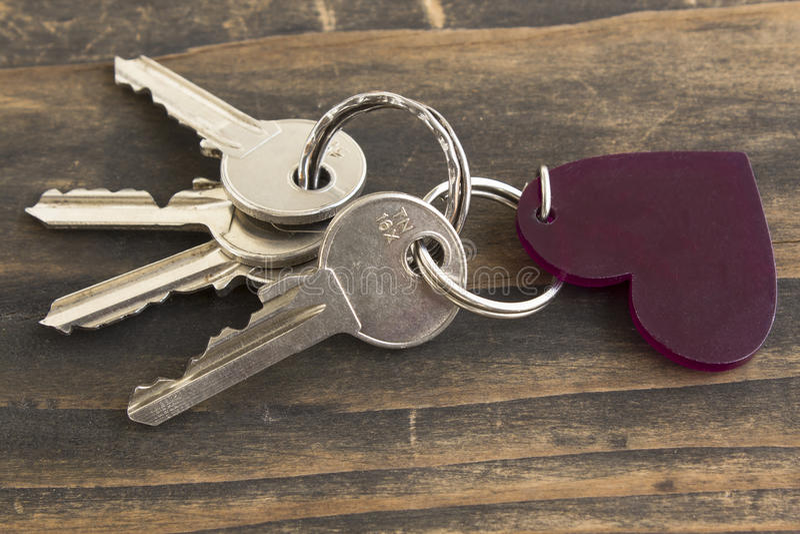 钥匙和心脏钥匙链在土气木背景 免版税库存图片