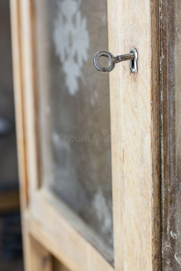 钥匙在老被插入餐具柜门 图库摄影