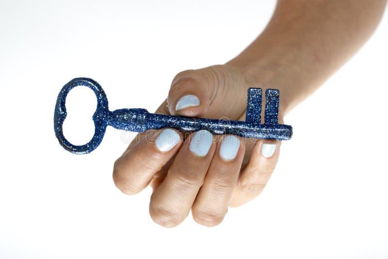 钥匙手中接触蓝色生活 免版税图库摄影