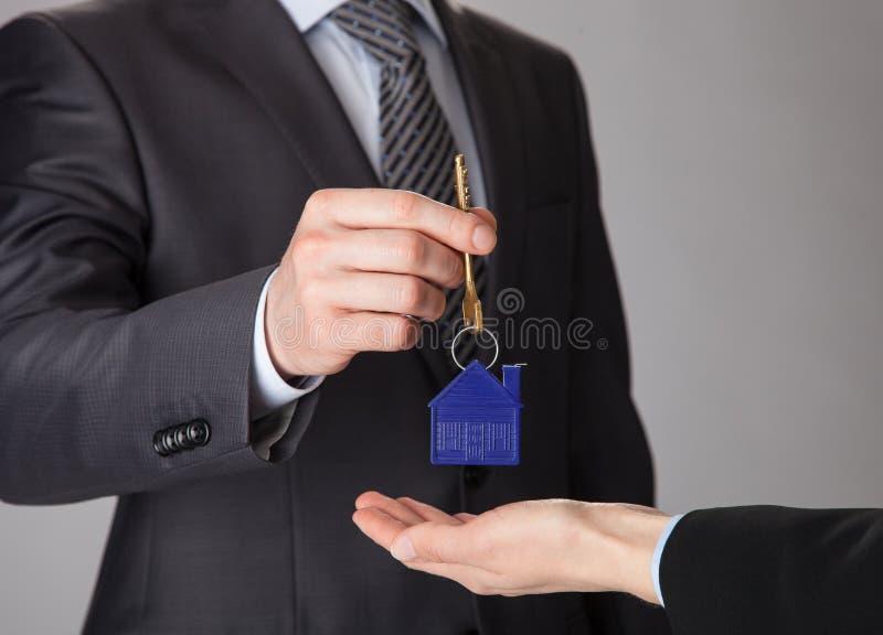给钥匙的商人妇女的手 免版税库存图片