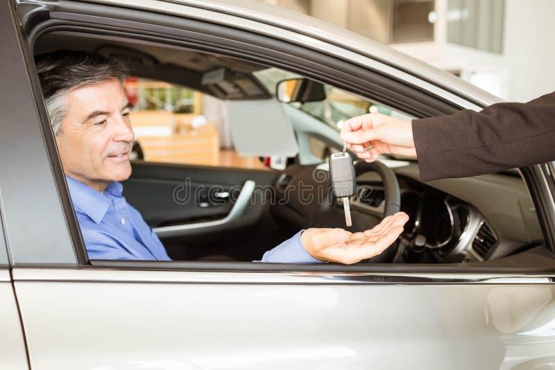 给钥匙的推销员一个微笑的商人 库存图片