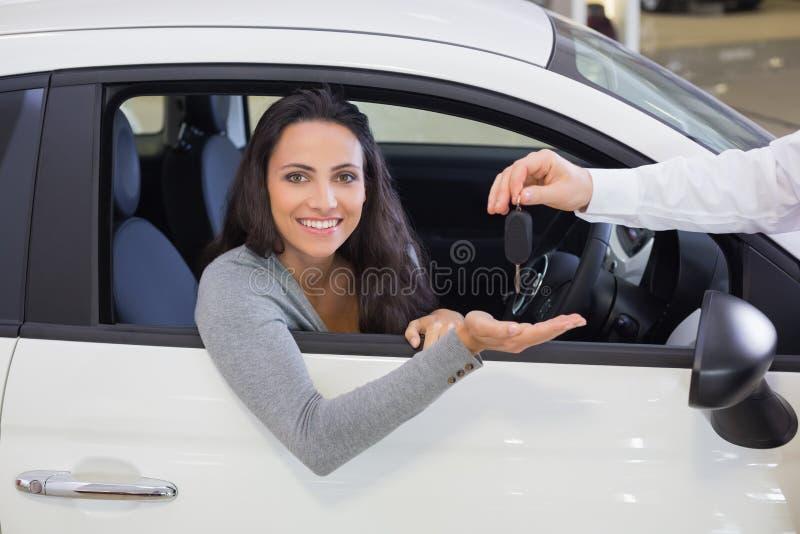 给钥匙的推销员一名微笑的妇女 库存图片