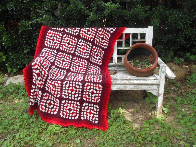 钩编编织物在长凳的毯子 免版税库存照片