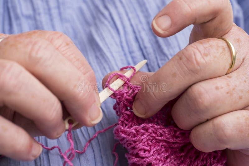 钩编编织物与象牙钩针编织的妇女的手 库存图片