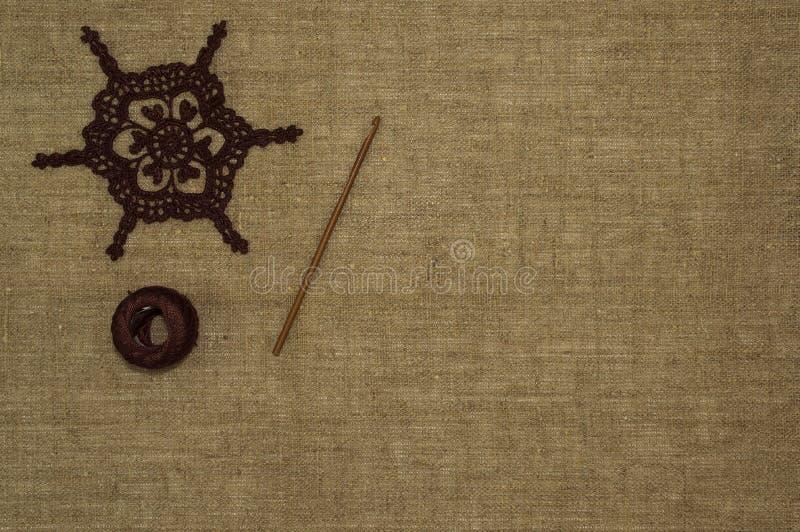 钩编编织物与钩针和棉纱品的小垫布鞋带在亚麻制背景 免版税库存照片