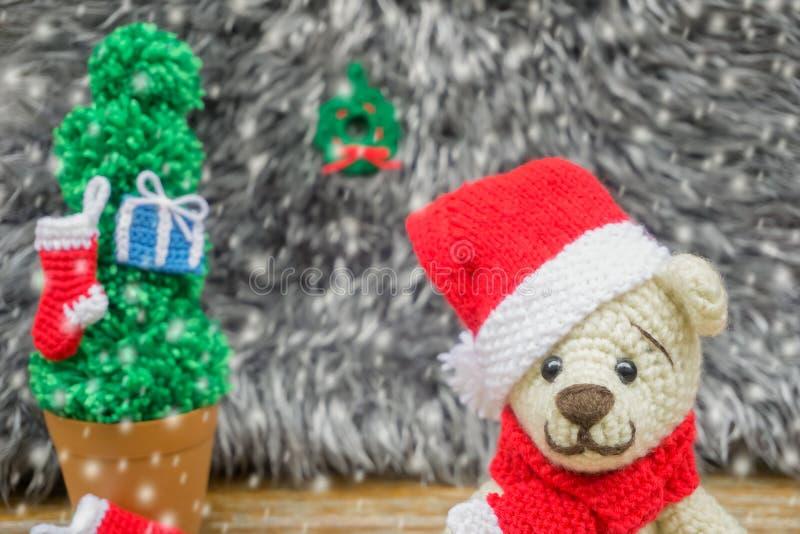 钩编编织物在一个红色圣诞节帽子的玩具熊 手工制造的amigurumi 库存照片