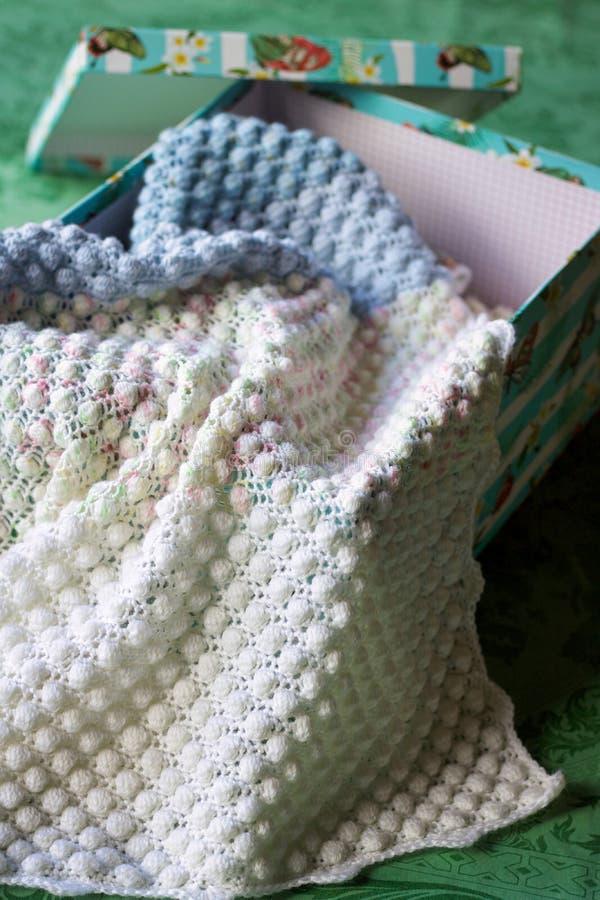 钩针编织在箱子的婴孩毯子 图库摄影