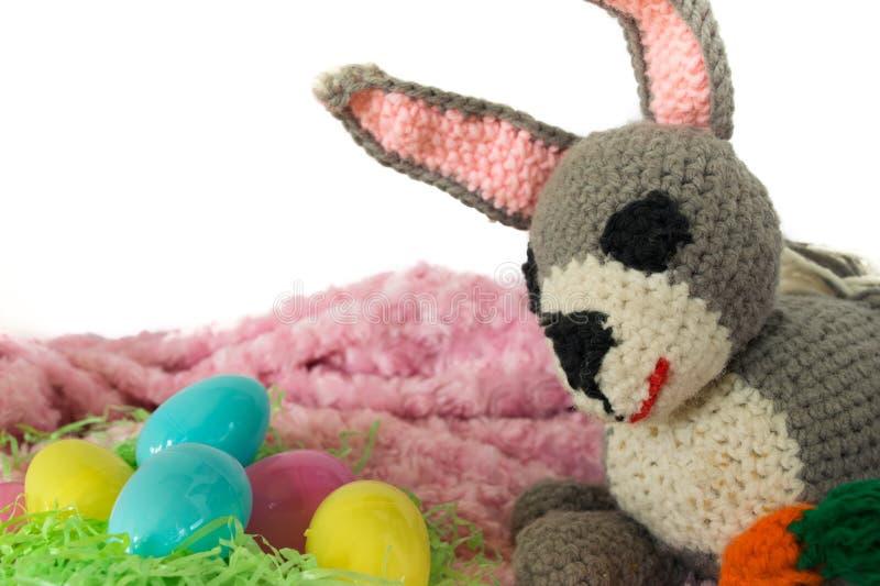 钩针编织的Amigurumi兔宝宝用在复活节显示旁边的红萝卜 库存图片