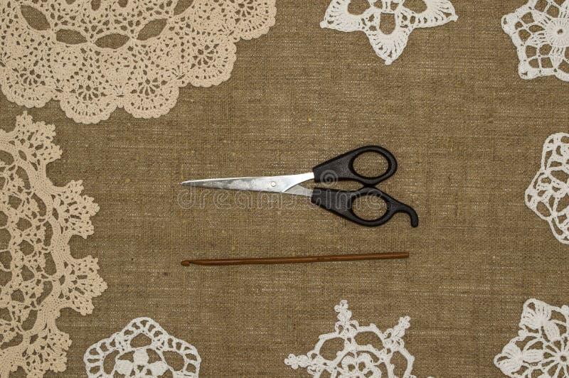 钩针编织在亚麻制背景的小垫布鞋带 免版税库存图片