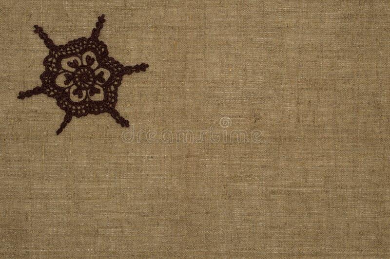 钩针编织在亚麻制背景的小垫布鞋带 库存图片
