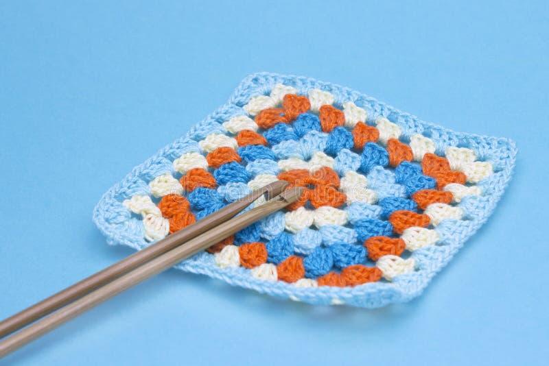 钩针编织手工制造老婆婆正方形和勾子 明亮的格子花呢披肩,毯子起点  五颜六色的原始的钩针编织手工制造工艺工作 库存图片