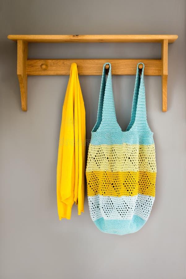 钩针编织的垂悬在墙壁机架的袋子和一块黄色毛巾 库存照片