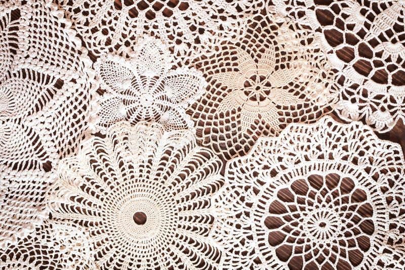 钩针编织餐巾美好的精美葡萄酒鞋带背景在桌上的 免版税库存照片