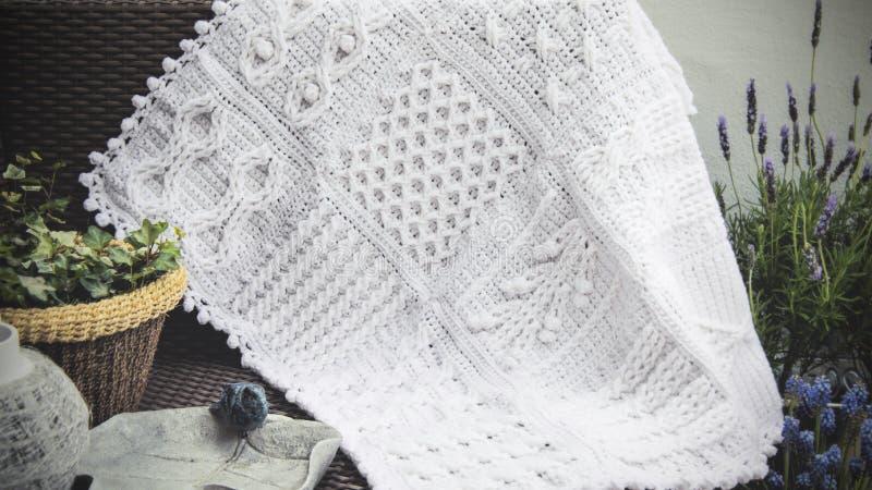 钩针编织,在白色的缆绳编织阿富汗婴孩毯子 免版税库存图片