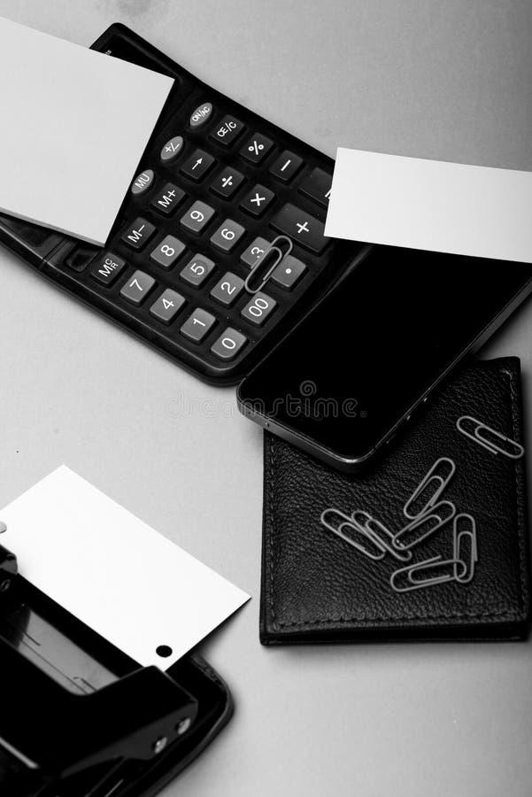 钱包、手机和打孔器在绿色背景 企业辅助部件和小配件概念 文具,钱包 免版税库存照片