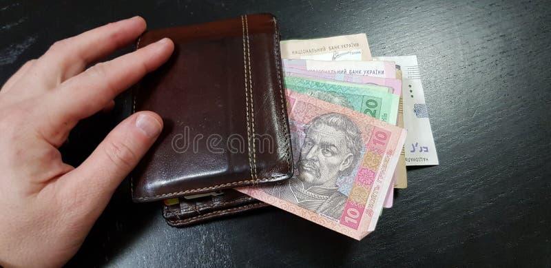 钱包充分与与男性手指的hryvnia钞票对此在黑桌放置 免版税库存照片