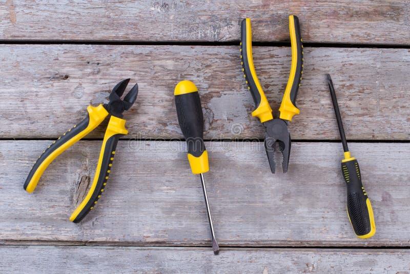 钳子和螺丝刀在木背景 免版税库存图片