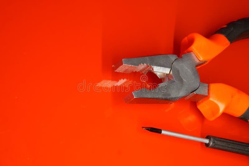 钳子和螺丝刀轻拍谎言红色优美的表面上在汽车修理店 技工的工作的设备和 免版税库存照片