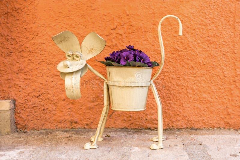 铁与紫色花的罐狗 库存照片