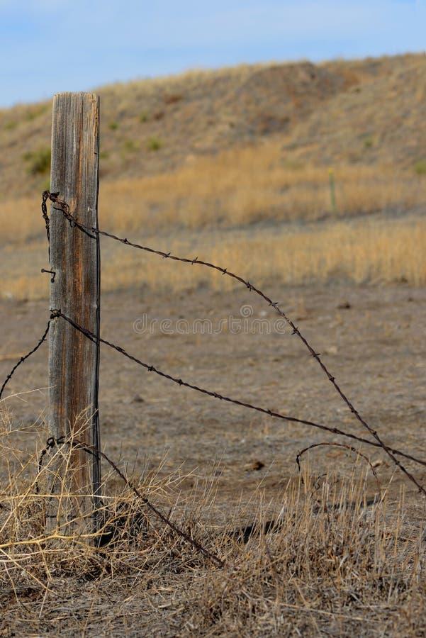 铁丝网和篱芭岗位有狂放的大草原背景 免版税库存图片