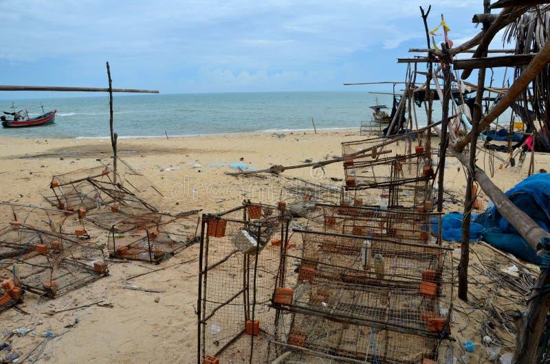 铁丝网方形框捕鱼网和小船在海边使村庄北大年泰国靠岸 免版税库存照片