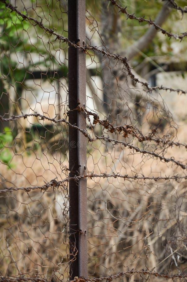 铁丝网被连接到生锈的篱芭 免版税图库摄影