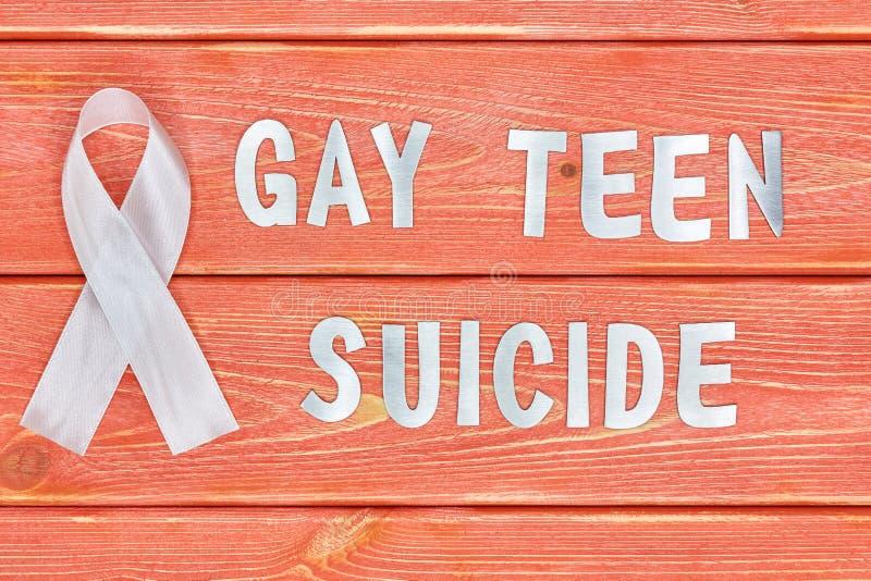 铁信件的白色了悟丝带和题字:快乐青少年的自杀,说谎在季节的木织地不很细背景颜色2019年 免版税库存照片