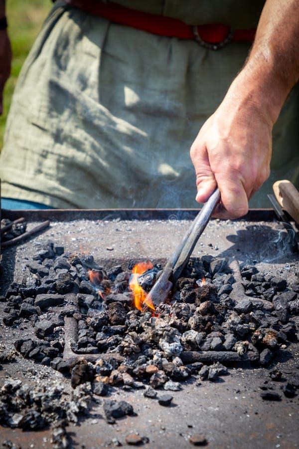 铁匠加热在炭烬的铁 免版税图库摄影