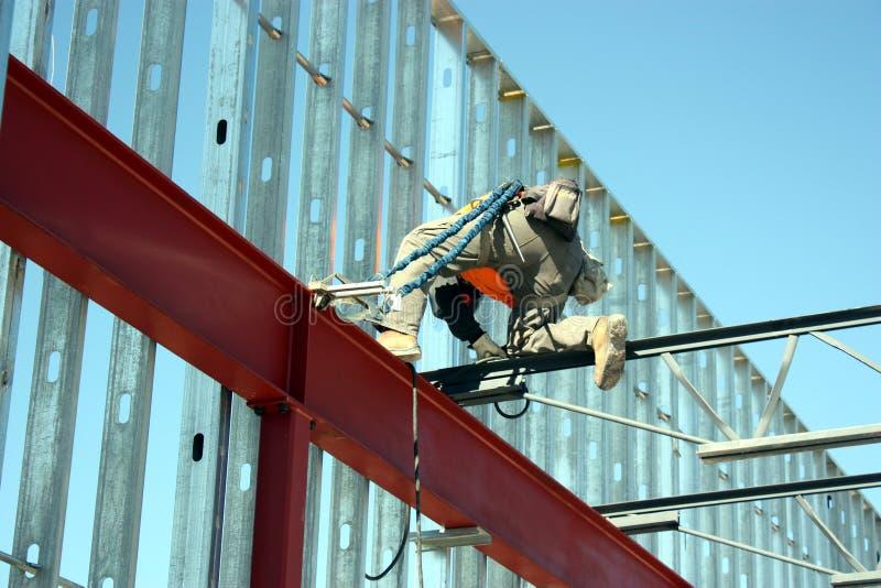 铁工作者焊接酒吧安装托梁 免版税库存照片