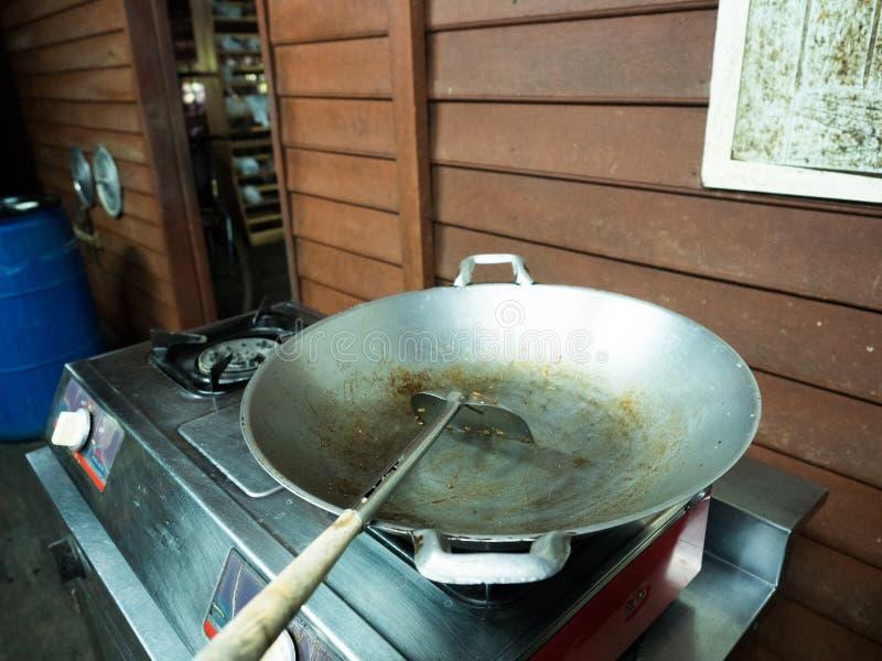 铁平底锅和特纳使用后在铝煤气炉在木厨房里 免版税库存照片