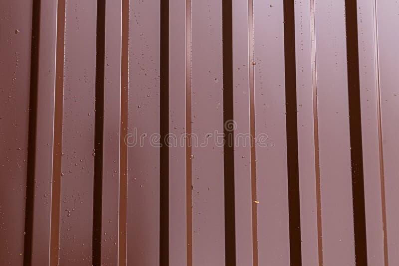 铁板料外形使垂直的平行的线成波状变褐发光的基地工业背景 库存图片
