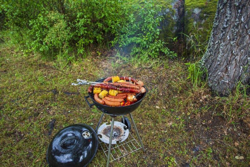 铁格栅接近的看法用香肠和玉米 烹调概念的室外食物 免版税库存图片