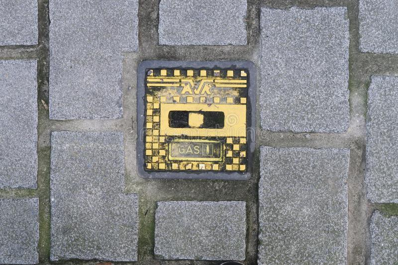 铁气体AVR人孔盖在一条走的街道的路面的在安特卫普 库存照片